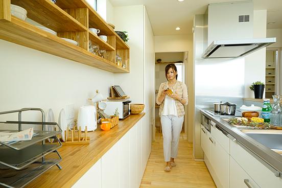 キッチン中心の家事動線計画は家事効率を上げるポイント。キッチンの背面収納には食器だけでなく裁縫箱、学校のプリントなど細々した家族で共有したいものの収納計画を提案しています。