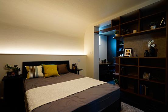 主寝室は打って変わってムーディーなテイストにコーディネートしました。間接照明やクロスにこだわり床材もシックに塗装しています。ベッド背面の壁から天井に向かってアールの壁を計画し、ベッドヘッドの間接照明が部屋全体を柔らかく照らします。